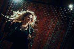 岩石` n `卷女孩,年轻美丽的妇女在黑暗的胡同跳舞,反对篱芭滤网 库存图片
