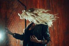 岩石` n `卷女孩,年轻美丽的妇女在黑暗的胡同跳舞,反对篱芭滤网 免版税库存照片