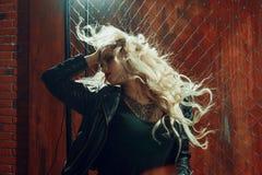 岩石` n `卷女孩,年轻美丽的妇女在黑暗的胡同跳舞,反对篱芭滤网 图库摄影