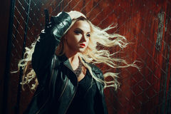 岩石` n `卷女孩,年轻美丽的妇女在黑暗的胡同跳舞,反对篱芭滤网 免版税图库摄影