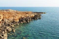 岸和岩石在平安的光滑的海 库存照片