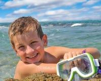 岸的微笑的男孩拿着潜水的一个面具 免版税图库摄影