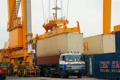 岸起重机在货物船的装货容器 免版税库存照片