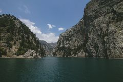 峡谷在潮流的清楚的水在岩石和溢出入一个巨大的水库之间 库存图片