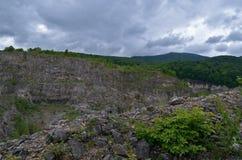 峭壁和山的看法 在前景的绿色灌木 免版税库存照片
