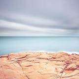 峭壁岩石、蓝色海洋和多云天空背景。 免版税库存照片