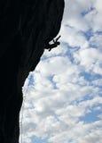 峭壁登山人上升的岩石剪影 免版税库存图片