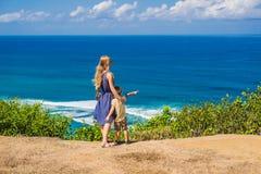 峭壁的妈妈和儿子旅客在海滩上 空的天堂 免版税图库摄影