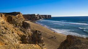 从峭壁的美丽的景色在与冲浪的波浪的海滩 免版税图库摄影