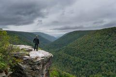 峭壁的边缘的远足者享受看法的 免版税库存照片