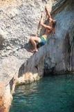 峭壁的面孔的年轻女性攀岩运动员 免版税库存照片