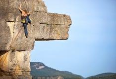 峭壁的年轻女性攀岩运动员 免版税库存图片