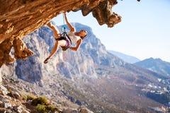 峭壁的年轻女性攀岩运动员 免版税图库摄影