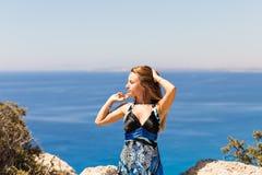 峭壁的年轻美丽的白种人女性在海上 免版税库存照片