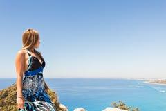 峭壁的年轻美丽的白种人女性在海上 图库摄影