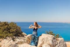 峭壁的年轻美丽的白种人女性在海上 免版税图库摄影