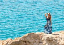 峭壁的年轻美丽的白种人女性在海上 库存图片