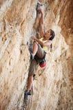 峭壁表面的新女性攀岩运动员 免版税库存图片