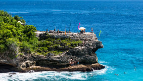 峭壁跳跃的地区 跳到水和放松在海滩的人们 免版税库存图片