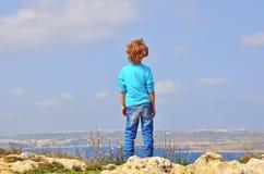 峭壁边缘的孤独的男孩 免版税库存图片