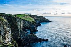 峭壁风景看法在爱尔兰海岸的与在日落的青山 免版税库存照片