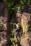 峭壁登山人紧贴的岩石 免版税库存照片