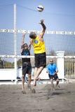 峰值 人跳跃的攻击 背景海滩查出的排球白色 图库摄影
