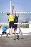 峰值 人跳跃的攻击 背景海滩查出的排球白色 库存照片