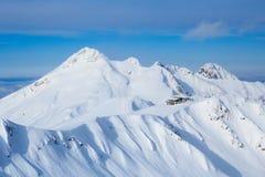 峰顶和咖啡馆在土坎的上面在多雪的高加索山脉在滑雪胜地 库存照片