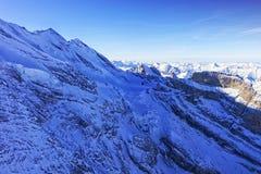 峰顶和coomb在少女峰地区直升机视图在冬天 图库摄影