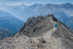 峰顶的步行者在南阿尔卑斯山 库存图片