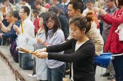 崇拜者在北京,中国拿着香火棍子并且祈祷在Yonghegong喇嘛寺庙 免版税库存图片