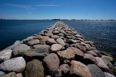 嵌入石头 多岩石的海滩,平安的海,港口 痣在Munalaid 图库摄影