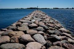 嵌入石头 多岩石的海滩,平安的海,港口 痣在Munalaid 免版税库存照片