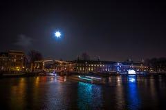 巡航在夜运河的小船仓促 阿姆斯特丹夜运河的轻的设施在轻的节日内的 图库摄影
