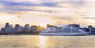 巡航在日落的小船航行在有蒙特利尔地平线的圣劳伦斯河背景的 免版税库存图片
