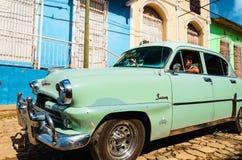 巡航在有五颜六色的房子的殖民地街道上的经典美国汽车在Trinidiad,老汽车 免版税图库摄影