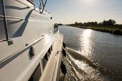 巡航在有太阳反射的一条运河的小船 库存图片