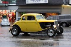 巡航在湿街道上的黄色旧车改装的高速马力汽车 库存图片
