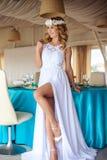 巡航婚姻的白色礼服的性感的年轻白肤金发的新娘在夏天海餐馆 免版税图库摄影