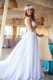 巡航婚姻的白色礼服的性感的年轻白肤金发的新娘在夏天海餐馆 库存照片