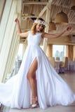 巡航婚姻的白色礼服的性感的年轻白肤金发的新娘在夏天海餐馆 图库摄影