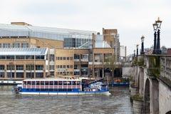 巡航沿泰晤士河的旅游蒸汽小船通过约翰・刘易斯商城和金斯敦桥梁在金斯敦在泰晤士, E 免版税库存照片