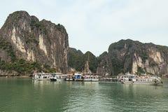 巡航的游船停止在鲜绿色水的石灰石海岛下与明亮的天空在夏天在广宁省,越南 免版税库存图片