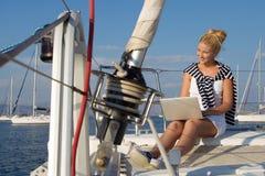 巡航:工作在小船的航行妇女。 库存图片