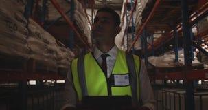巡逻仓库走廊的男性仓库工作者在晚上4k 影视素材