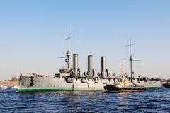 巡洋舰极光的拖曳费对修理地方的在船坞,圣彼德堡,俄罗斯 免版税图库摄影