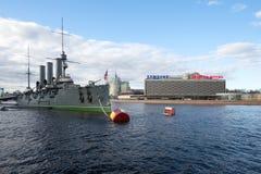 巡洋舰`极光`和旅馆`圣彼德堡`在多云天空下在5月下午 免版税库存图片