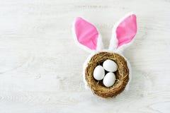 巢用三个白色复活节彩蛋和兔宝宝耳朵在家在复活节天 免版税库存照片
