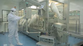 工业制药 检查药片的质量的男性工厂劳工包装在配药工厂 贪婪 图库摄影